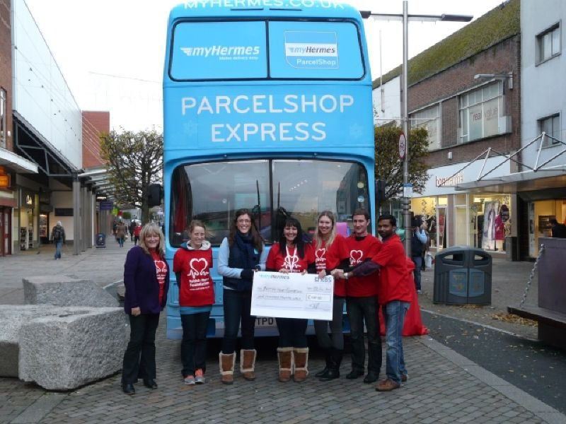 Outside the exhibition bus presenting a cheque